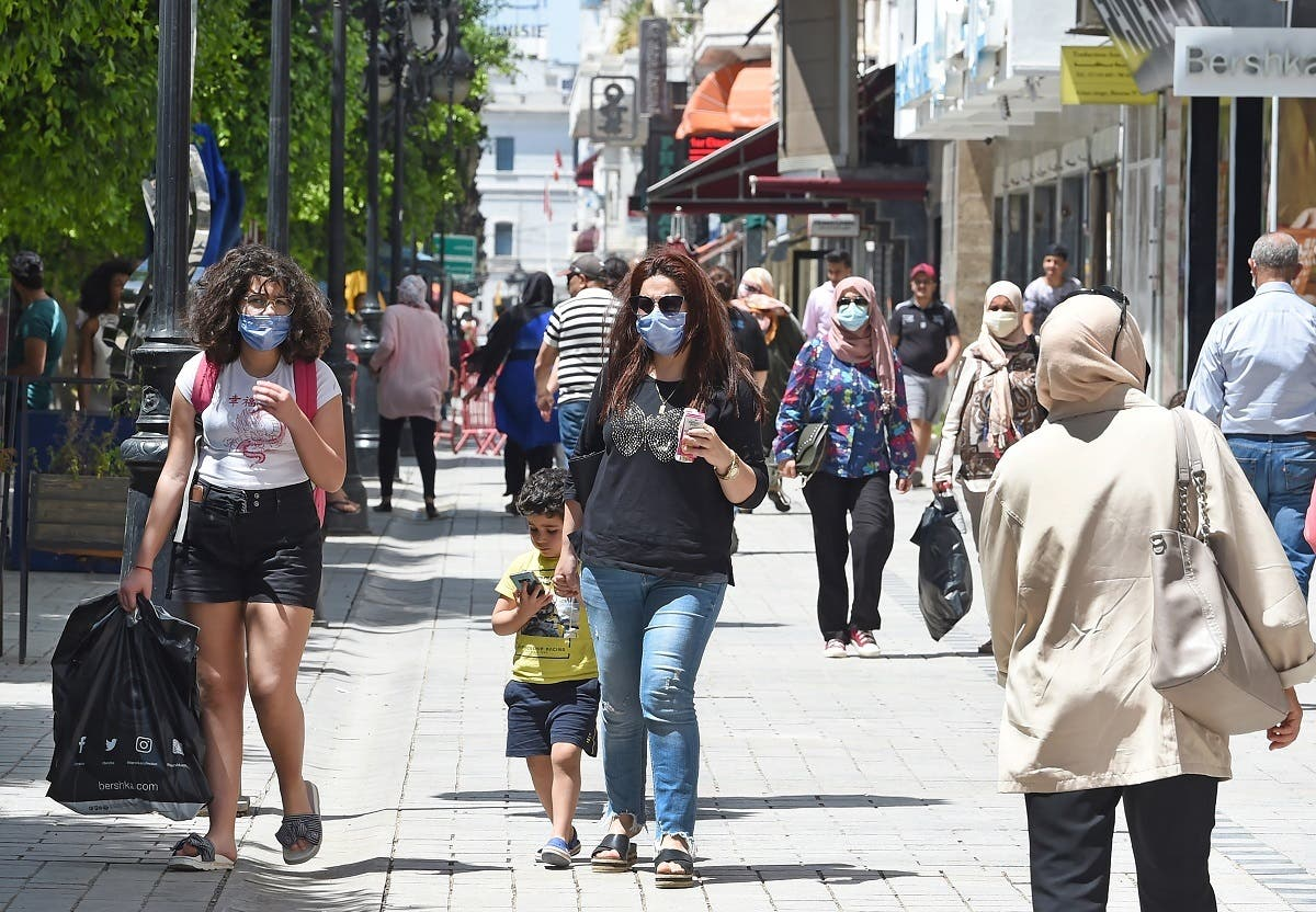 Tunisians walk in the Habib Bourguiba avenue in the capital Tunis on May 12, 2020, following the easing of the lockdown measures to combat the spread of coronavirus. (AFP)