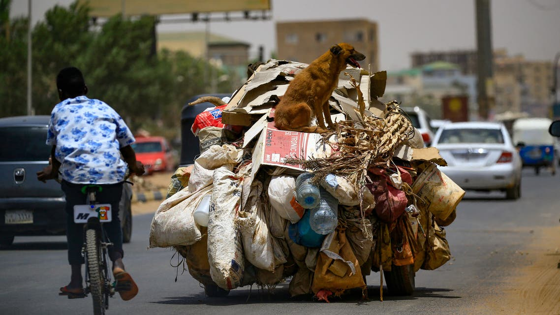 A young Sudanese boy rides his bicycle past a vehicle transporting domestic garbage, in the capital Khartoum, on April 9, 2020. (AFP)