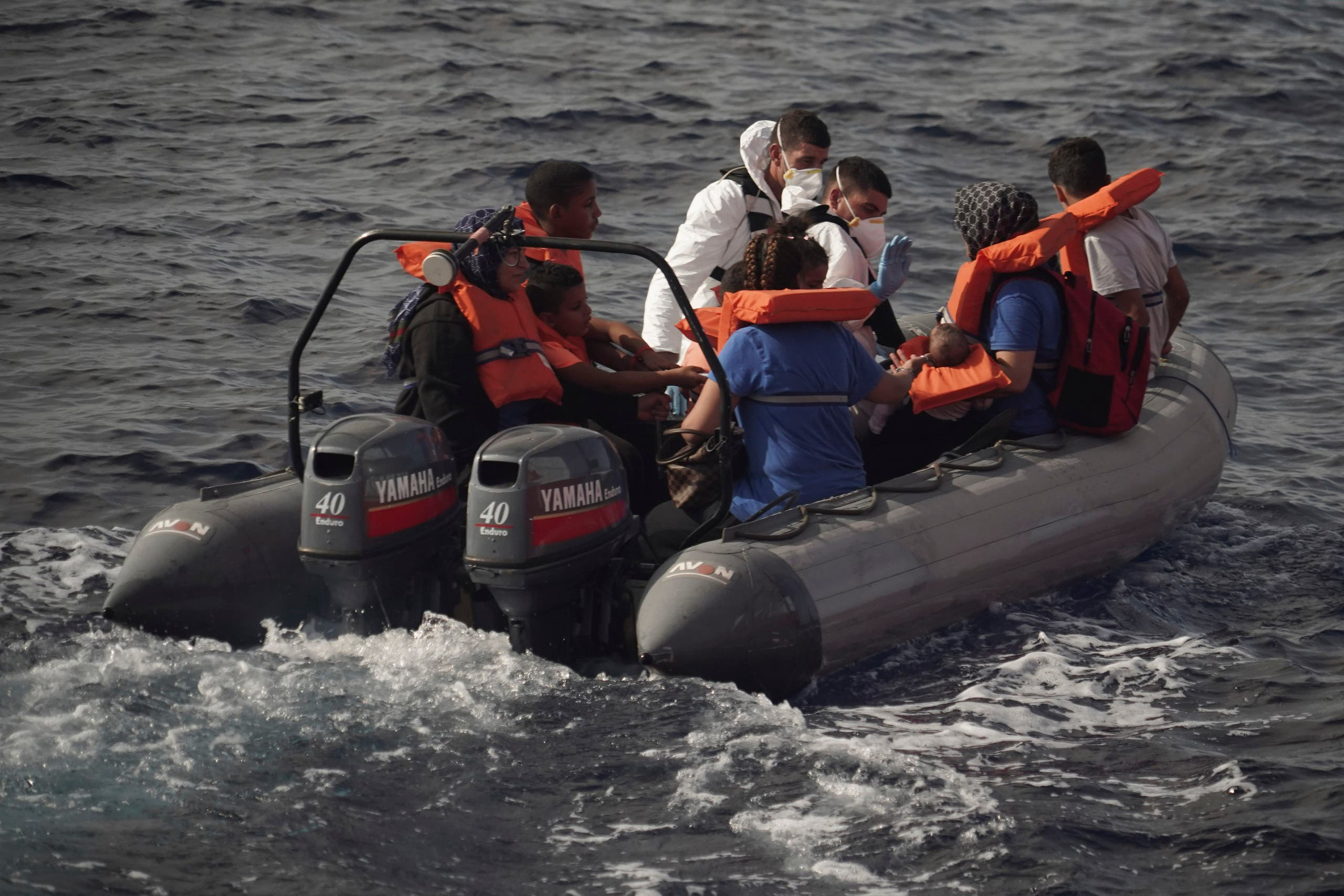 Members of the Maltese Armed Forces take a group of migrants to a Maltese military ship in the Mediterranean Sea, on September 20, 2019. (AP)