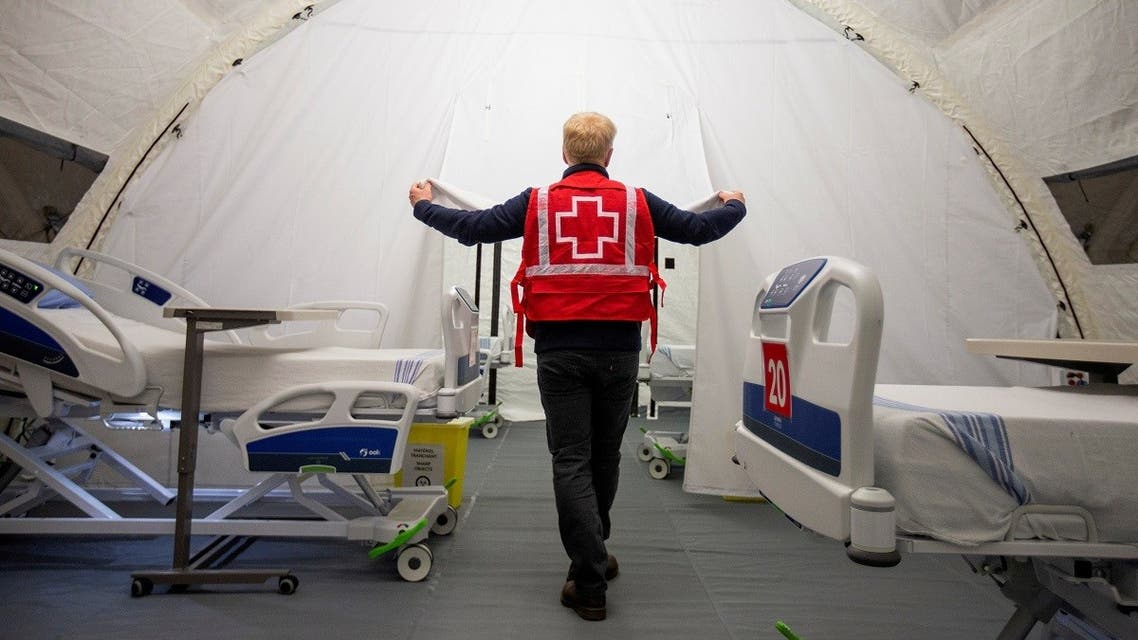 A volunteer with the Red Cross shows a doorway between beds in a mobile hospital set up in partnership with the Canadian Red Cross in the Jacques-Lemaire Arena to help care for patients with the coronavirus disease in Montreal. (File photo: Reuters)