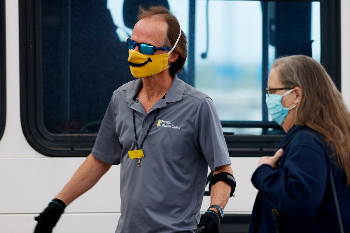A shuttle driver for Hertz, left, wears a face mask with a built-in smile as he helps a traveler board the bus outside the main terminal at Denver International Airport as easing of restrictions of the new coronavirus start, Wednesday, May 13, 2020. (Reuters)