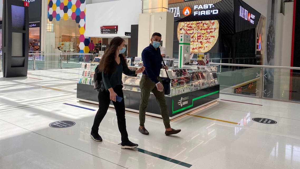 People wearing protective face masks walk at Dubai mall, following the outbreak of the coronavirus in Dubai, United Arab Emirates, May 3, 2020. (Reuters)