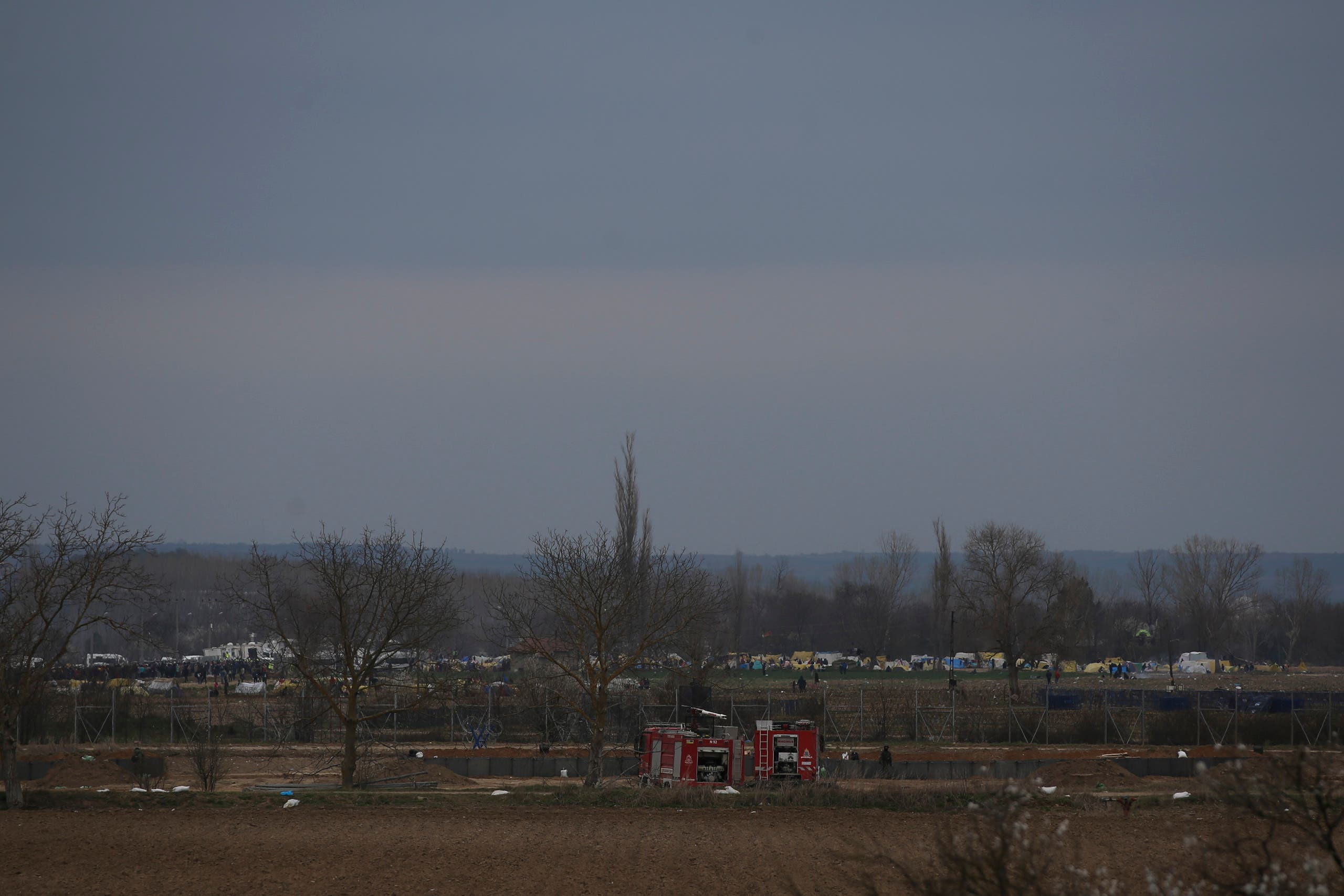 Migrants gather in tends at the Pazarkule crossing point in the Turkish side of the Greek-Turkish border near the village of Kastanies, Evros region, Greece, on Tuesday, March 10, 2020. (AP)