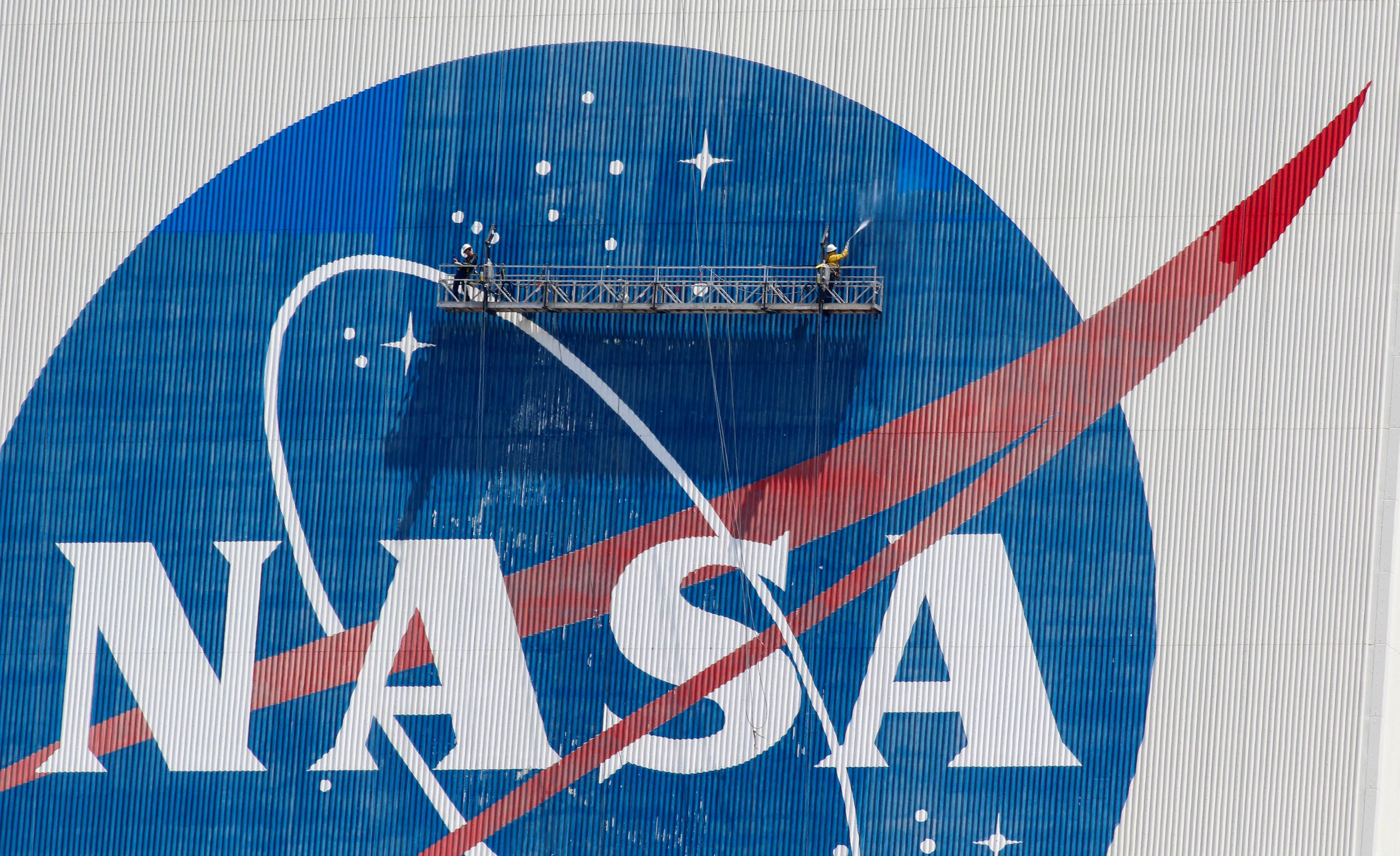 Workers pressure wash the logo of NASA on the Vehicle Assembly Building before SpaceX will send two NASA astronauts to the International Space Station aboard its Falcon 9 rocket, at the Kennedy Space Center in Cape Canaveral, Florida, U.S., May 19, 2020. (Reuters)