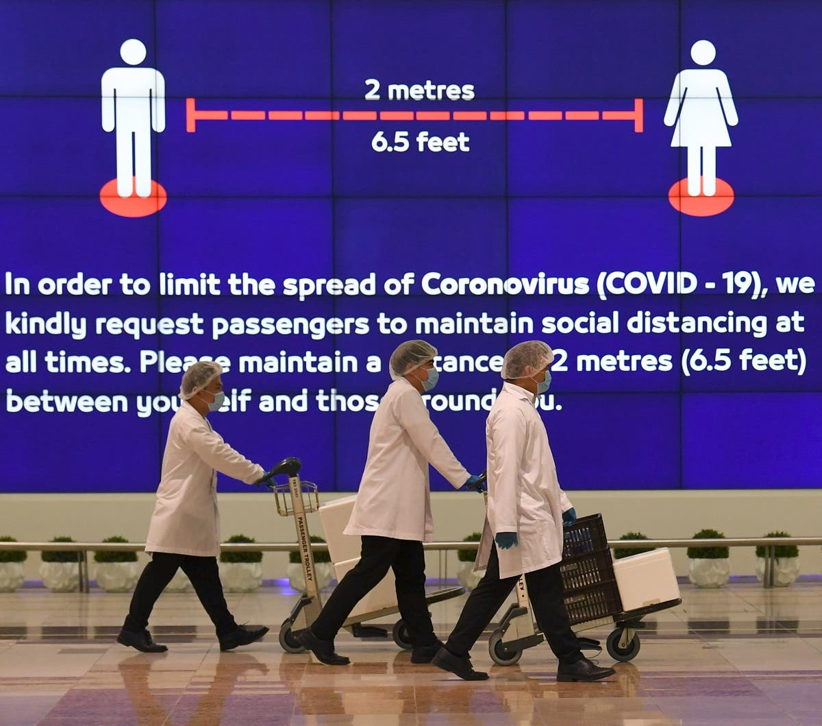 Employees at Dubai International Airport, walk past a poster reminding passengers to keep a safe distance from each other, after the resumption of scheduled operations by the Emirati carrier Emirates airline, amid the ongoing novel coronavirus pandemic crisis, on May 22, 2020. (AFP)