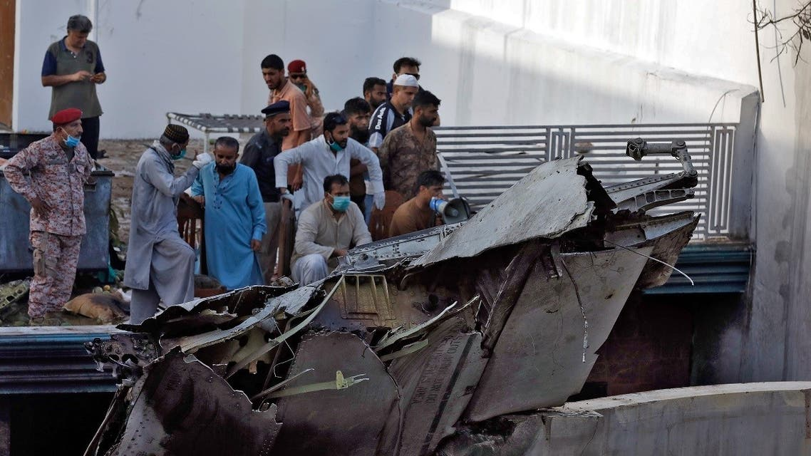 People stand next to the debris of a plane after crashed in a residential area near an airport in Karachi. (Reuters)