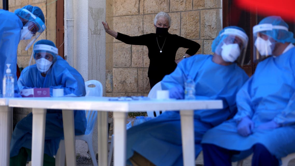 An elderly woman waits to be tested for the novel coronavirus by a nurse with the mobile crew of the Lebanese American University Medical Center, at the Order of Malta dispensary, in the southern Lebanese local authority of Roum in the town of Jezzine on May 21, 2020.