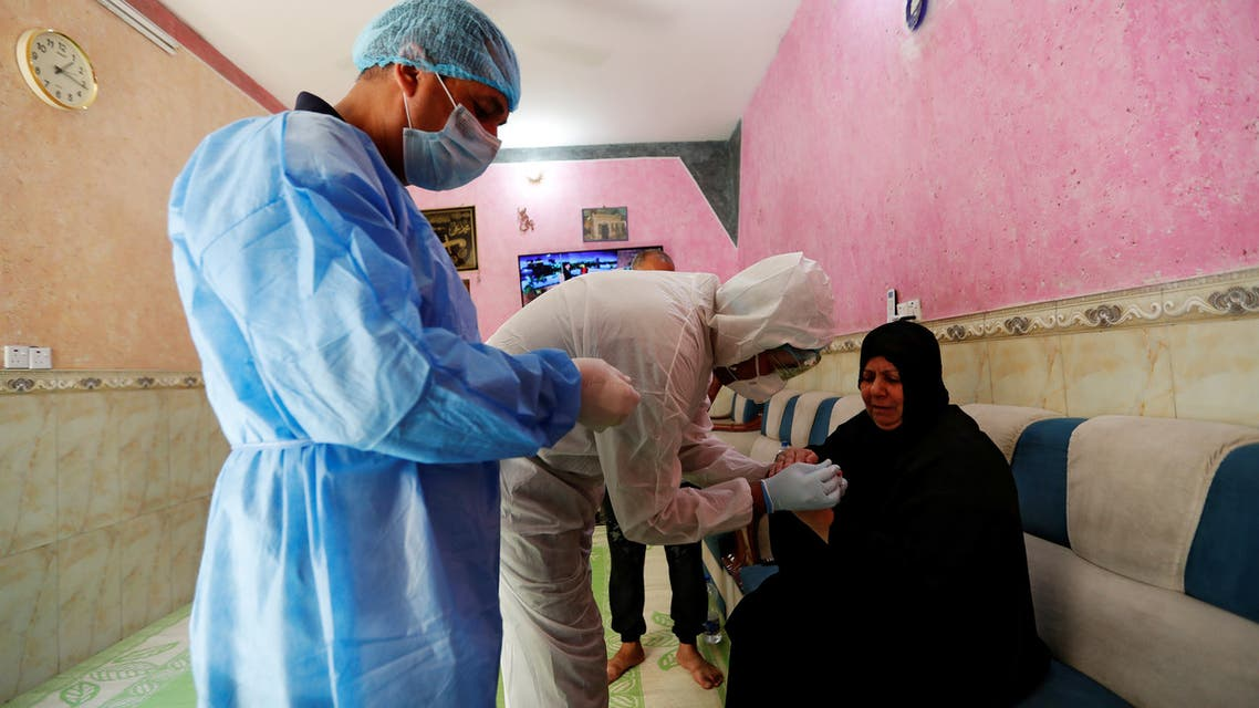 A healthcare worker takes blood samples from a woman during testing for the coronavirus disease (COVID-19) in Sadr city, district of Baghdad, Iraq May 21, 2020. REUTERS/Thaier Al-Sudani