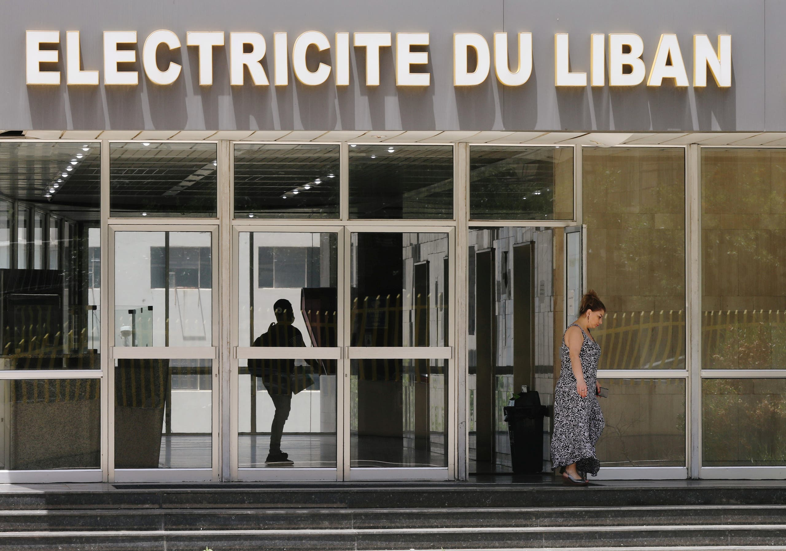A woman walks outside a building of a Lebanon's electricity company in Beirut, Lebanon May 20, 2020. (Reuters)