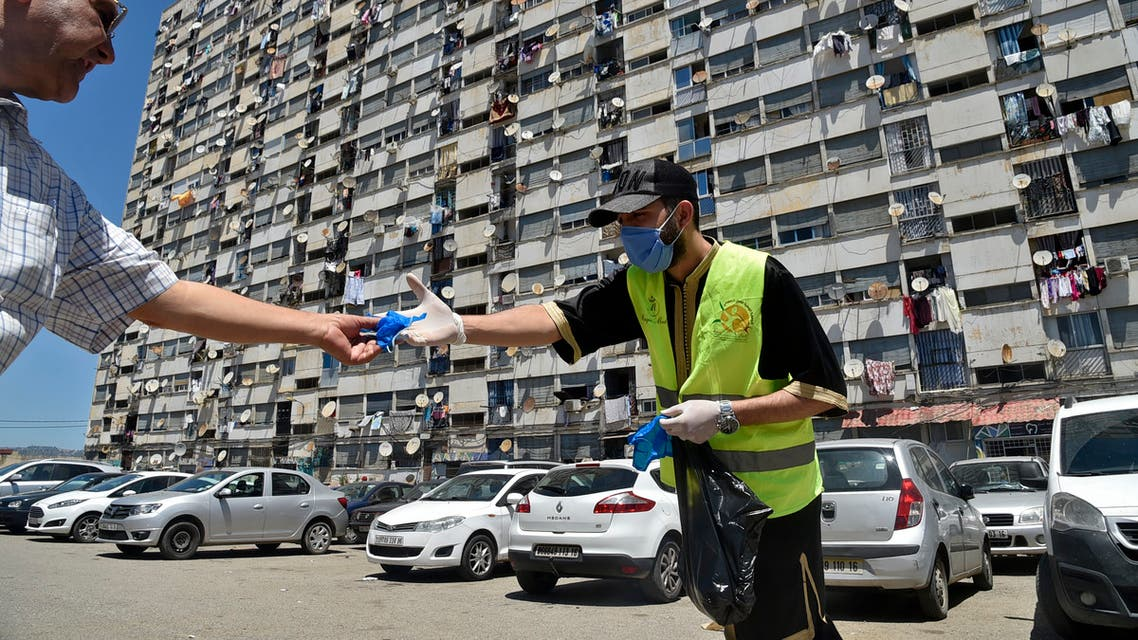 Algerians receive masks distributed by volunteers from the civil society, in a neighbourhood of the capital Algiers on May 21, 2020, as the threat of infections by the COVID-19 caused by the novel coronavirus lingers in the country.