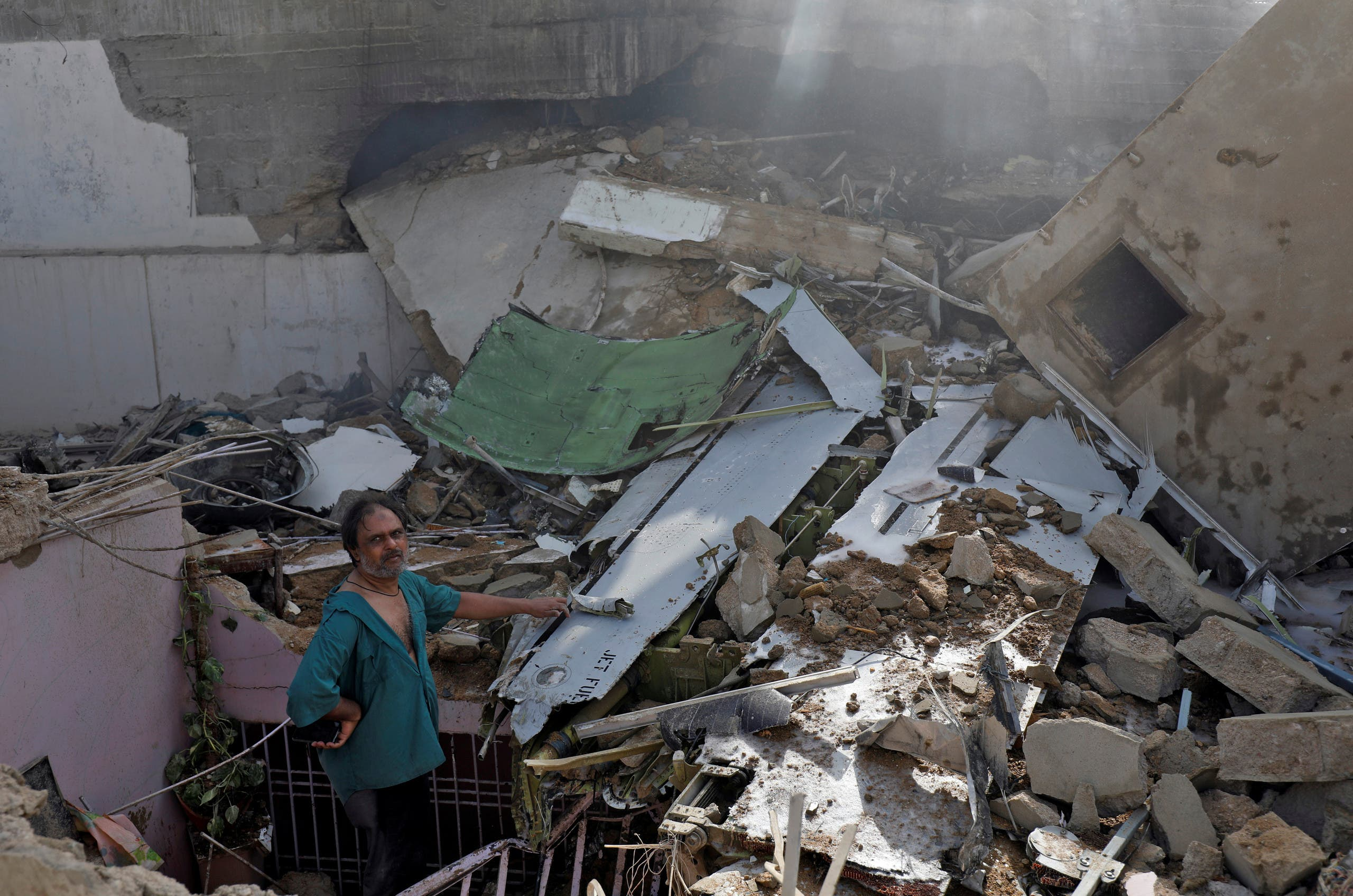 A man stands on the debris of a house at the site of a passenger plane crash in a residential area near an airport in Karachi, Pakistan May 22, 2020. (File photo: Reuters)