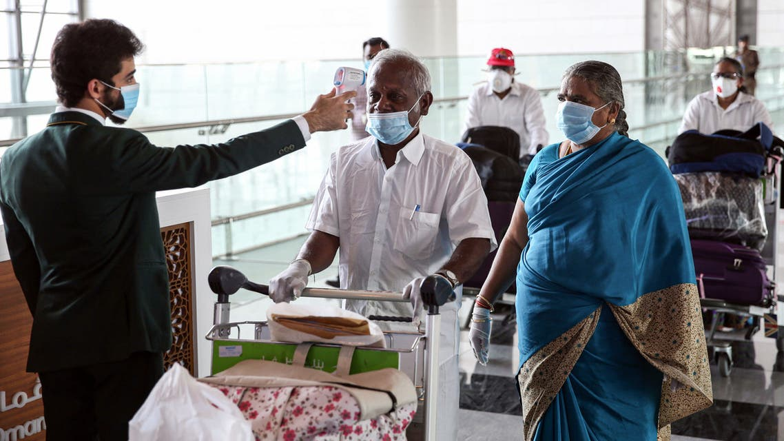 Indian nationals residing in Oman, wearing face masks due to the COVID-19 coronavirus pandemic, have their body temperatures measured at a terminal in Muscat International Airport ahead of their repatriation flight from the Omani capital, on May 12, 2020.