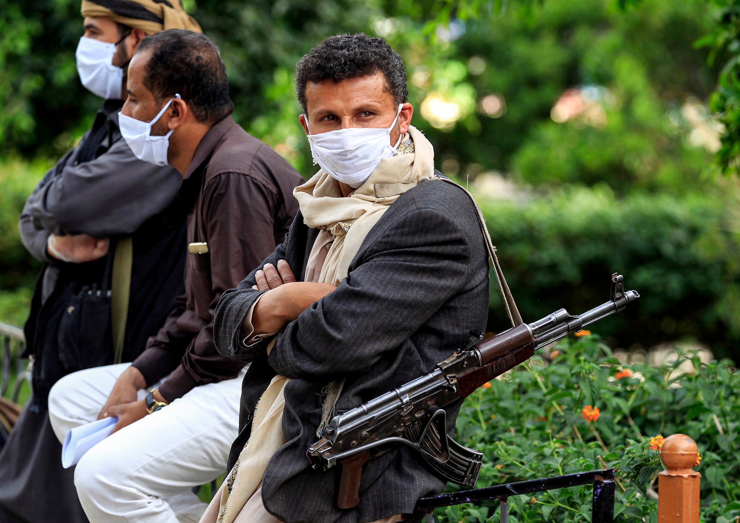 A fighter loyal to Yemen's Houthi rebels acting as security, looks on while wearing a face mask and latex gloves and slinging a Kalashnikov assault rifle as volunteers part of a community-led initiative to prevent the spread of COVID-19 coronavirus disease gather in Yemen's capital Sanaa on May 14, 2020. (AFP)