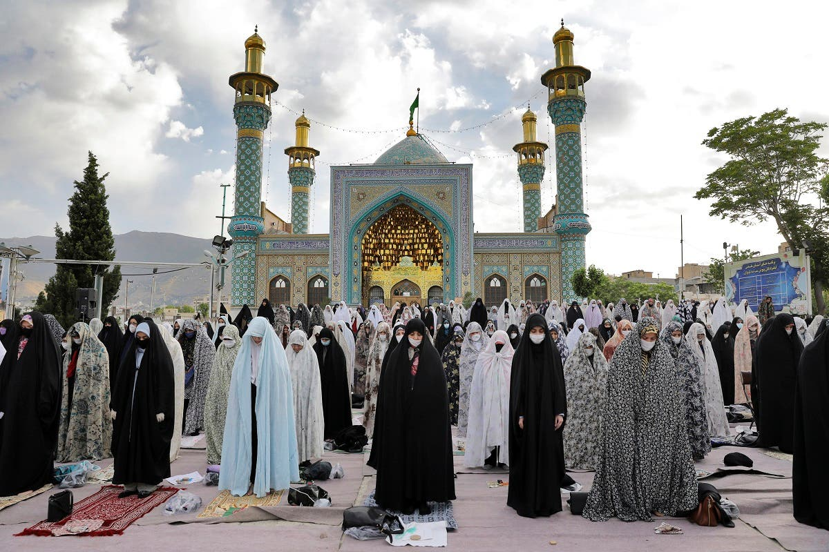 Worshippers wearing protective face masks and gloves offer Eid al-Fitr prayers outside a shrine to help prevent the spread of the coronavirus, in Tehran, Iran, Sunday, May 24, 2020. (AP)