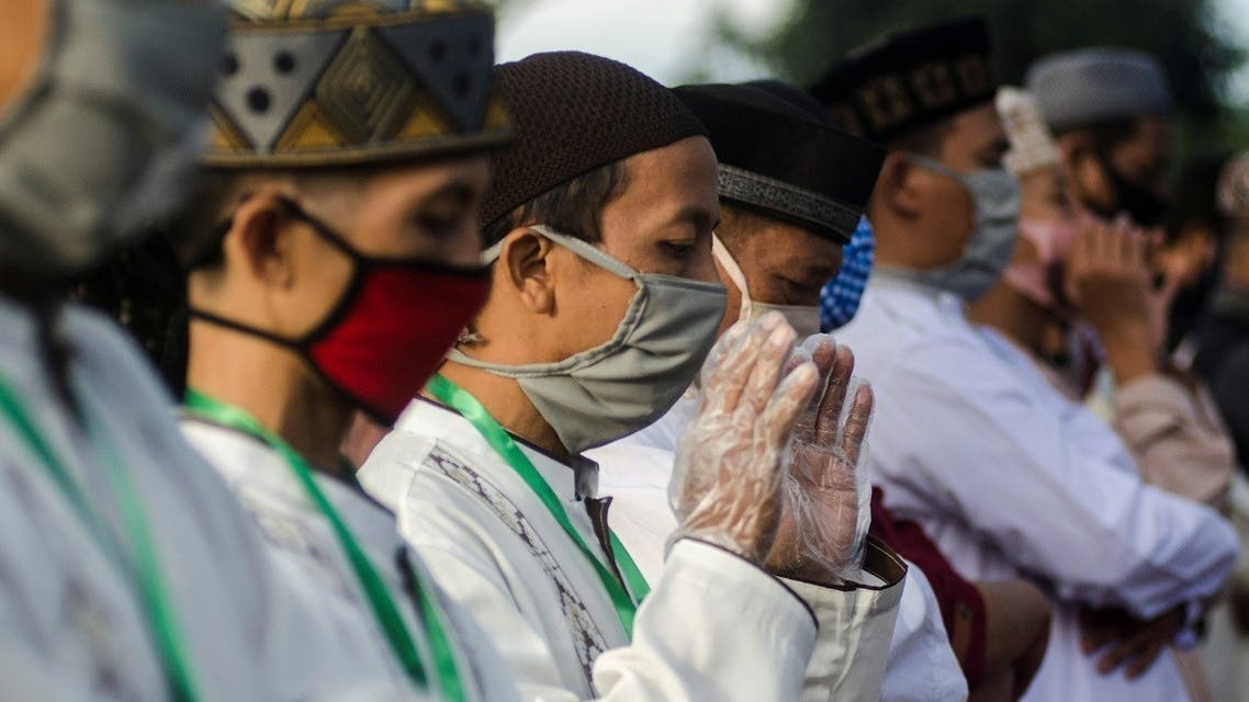Indonesian Muslims wear protective face masks and plastic gloves as they pray at a mosque during Eid al-Fitr on May 24, 2020. (Reuters)