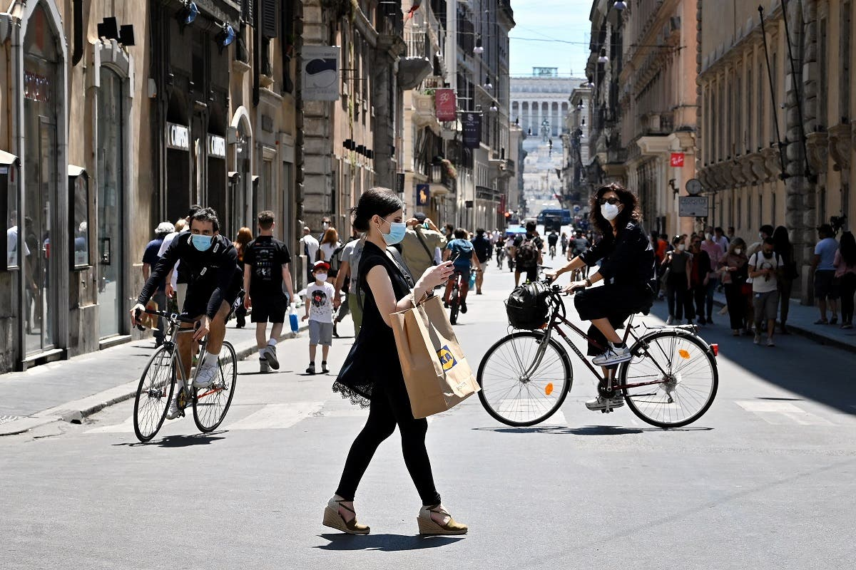 A woman wearing a protective mask walks in via Del Corso central Rome, on May 23, 2020. (AFP)