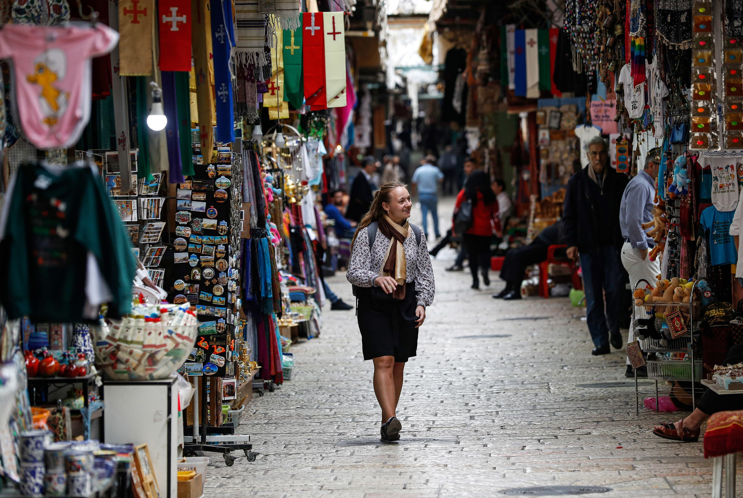 A lone tourist makes her way along a market street in the nearly deserted Old City of Jerusalem on March 12, 2020. (AFP)