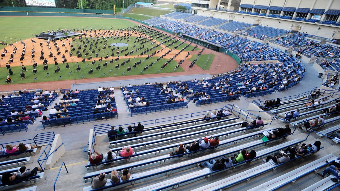 Seniors at Spain Park High School sit on a baseball field during a socially distanced graduation ceremony in Hoover, Alabama, on Wednesday, May 20, 2020. (AP)