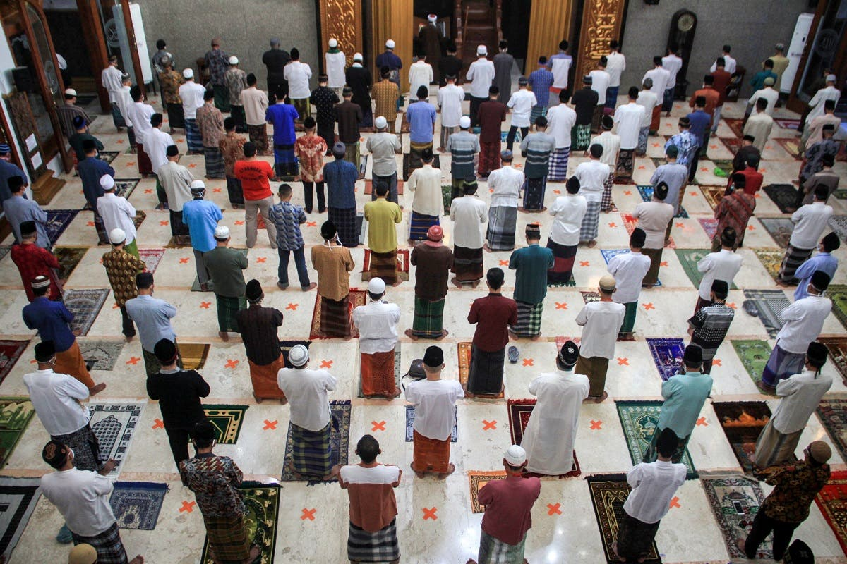 Indonesian Muslims take part in prayers at a mosque during Eid al-Fitr while maintaining social distancing. (Reuters)