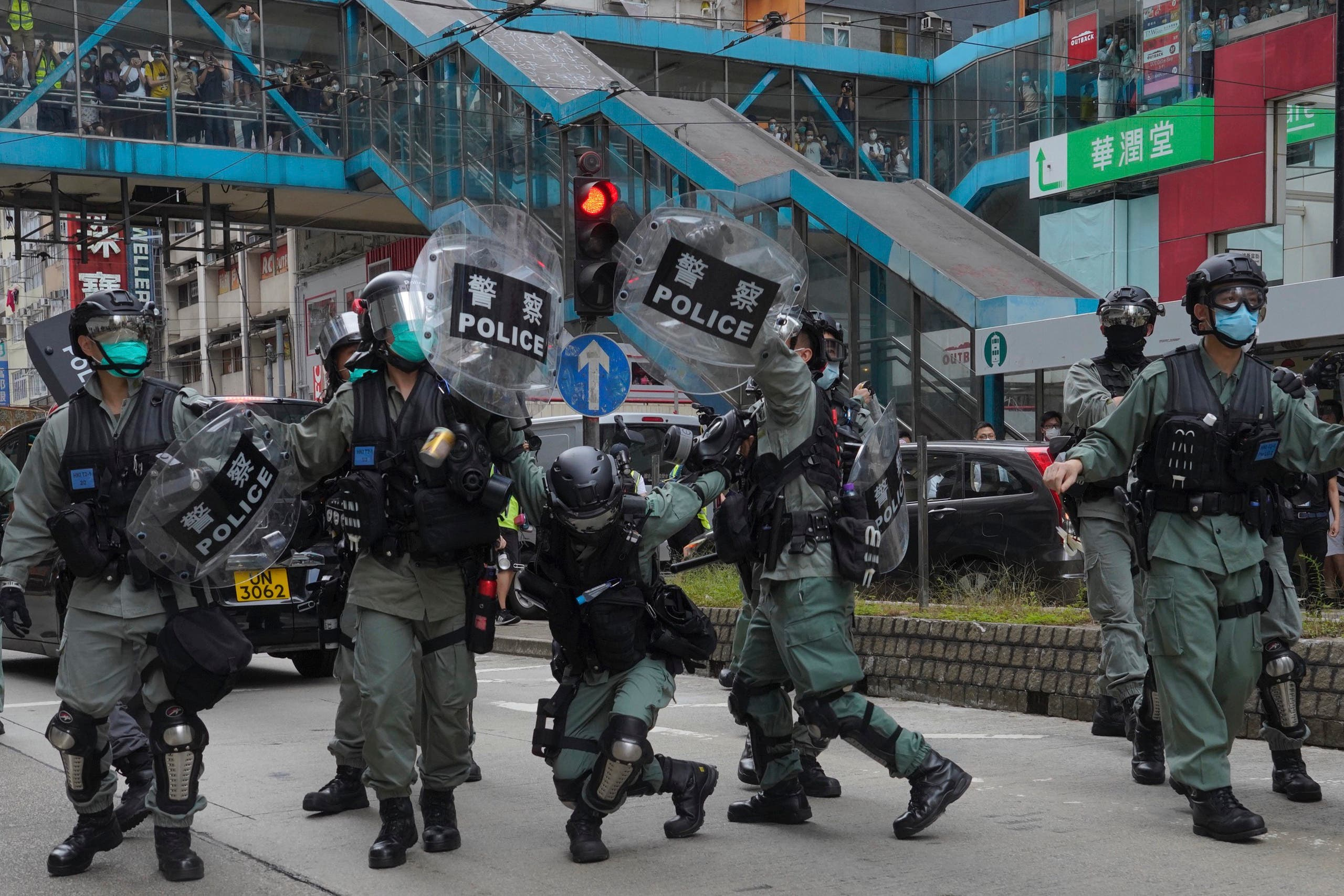 Riot police cover themselves with shields as hundreds of protesters march along a downtown street during a pro-democracy protest against Beijing's national security legislation in Hong Kong, on May 24, 2020. (AP)