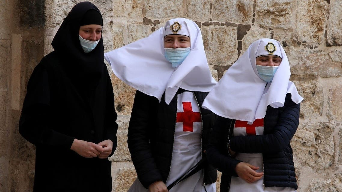 Christian nuns wearing face masks stand outside the shut doors of the Church of the Holy Sepulchre in Jerusalem's Old City on May 24, 2020, closed due to the coronavirus pandemic lockdown. (AFP)