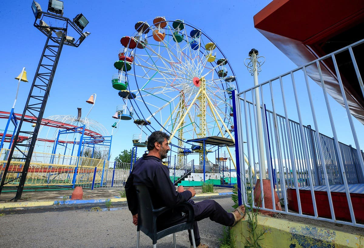 A security guard sits at an empty amusement park, on the first day of the Muslim holiday of Eid al-Fitr, in Sidon, southern Lebanon. (Reuters)