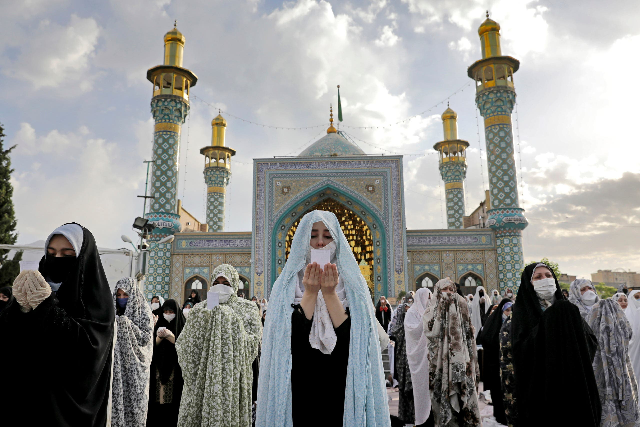 Worshippers wearing protective face masks offer Eid al-Fitr prayers outside a shrine to help prevent the spread of the coronavirus, in Tehran, Iran on May 24, 2020. (AP)