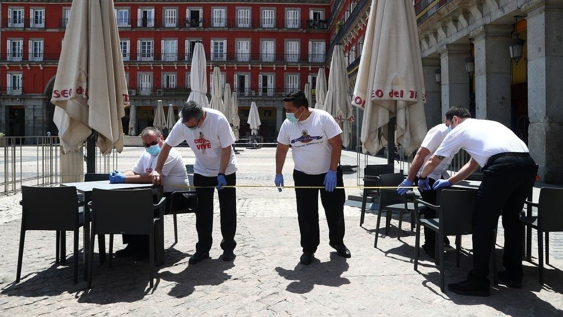 Workers use measuring tape to check social distancing as they set up a terrace which will be allowed to open from May 25, amid the coronavirus disease (COVID-19) outbreak, at Plaza Mayor Square in Madrid, Spain, May 24, 2020. (Reuters)