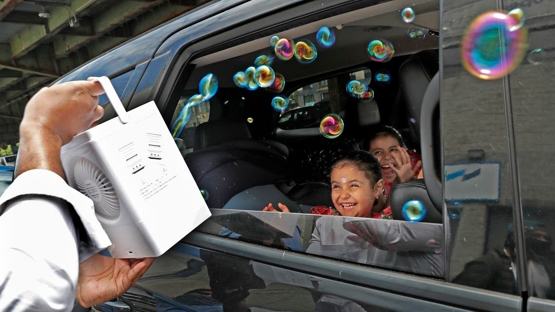 Children react from inside their family's car as a volunteer from the Muslim Community Center blows bubbles at them as part of an Eid al-Fitr celebration in Brooklyn, May 24, 2020, in New York. (AP)