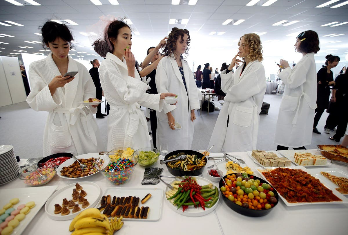 Models eat food backstage before Christian Dior's Haute Couture Spring-Summer 2017 live show to celebrate Dior's new flagship store at the Ginza Six mall in Tokyo, Japan, April 19, 2017. (Reuters)