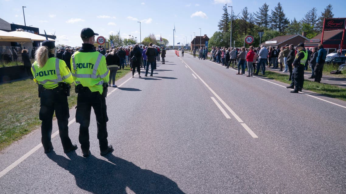 Policemen watch protesters standing on a street connecting Denmark and Germany during a demonstration at the border crossing in Saed, near Toender, Denmark, on May 17, 2020, asking to open the border between Denmark and Germany. Denmark closed its borders towards Sweden and Germany on March 14, 2020, in a measure to limit the spread of the new coronavirus / COVID-19 pandemic.