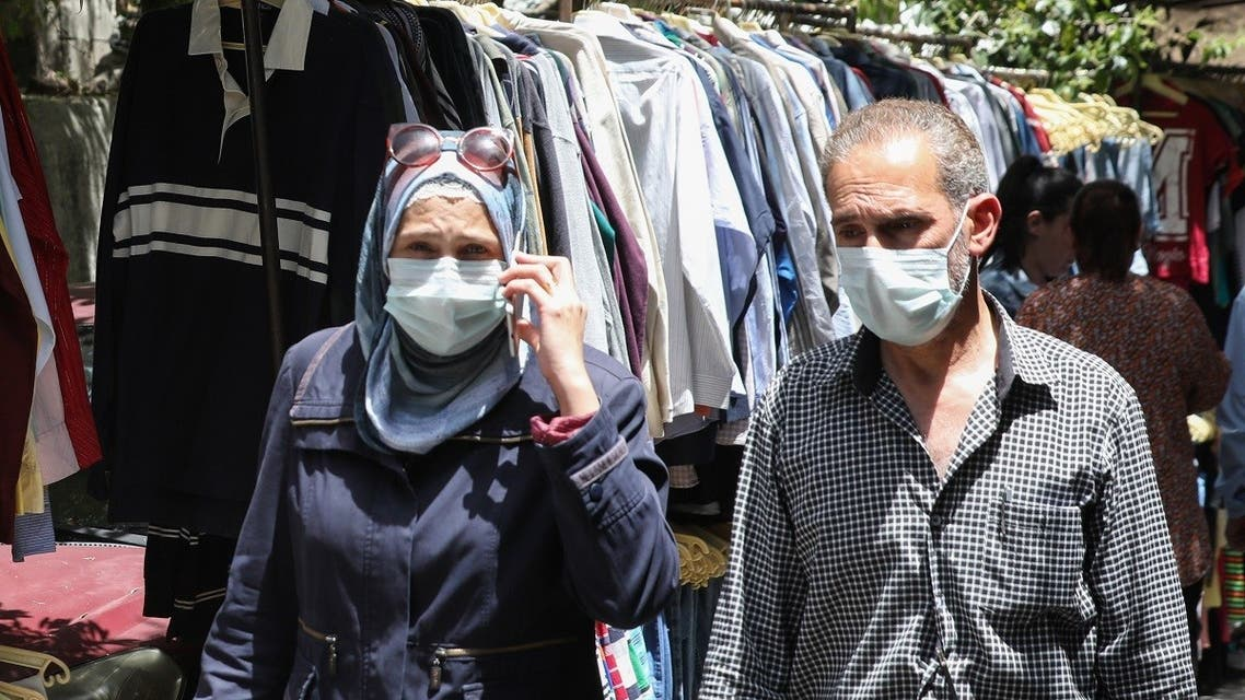 Mask-clad Syrians shop for clothes at a flea market in the capital Damascus on May 17, 2020. (AFP)