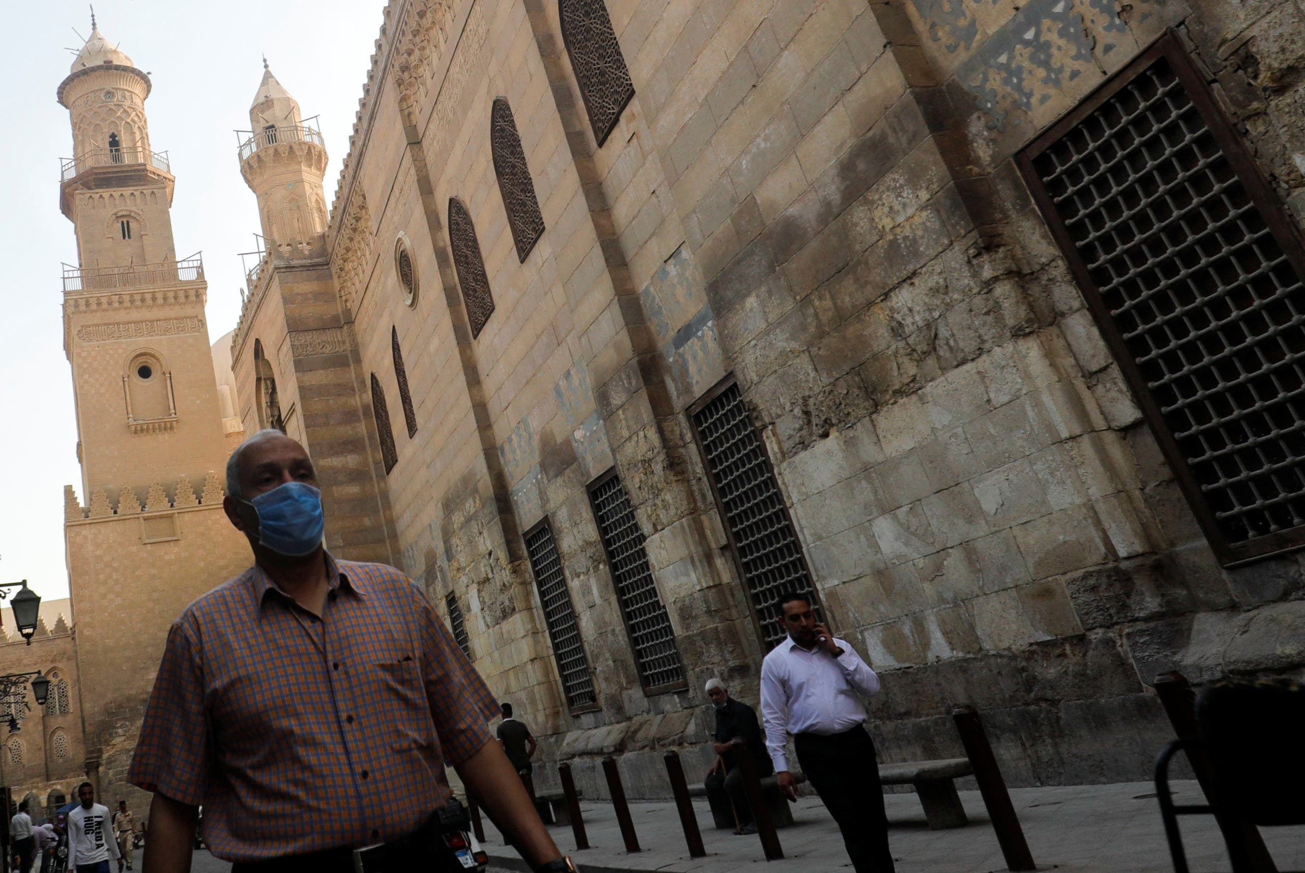 A man wearing a protective face mask walks next to others in front of closed mosques in old Cairo, Egypt. (Reuters)