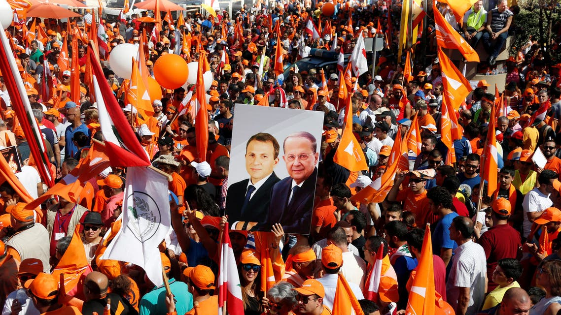 Supporters of the Free Patriotic Movement (FPM) carry flags and a picture of Christian politician and FPM founder Michel Aoun (R) and Lebanese Foreign Minister and head of the Free Patriotic Movement (FPM) Gebran Bassil, during a rally to show support for Aoun and calling to elect a president, near the presidential palace in Baabda, near Beirut, Lebanon October 16, 2016. (Reuters)