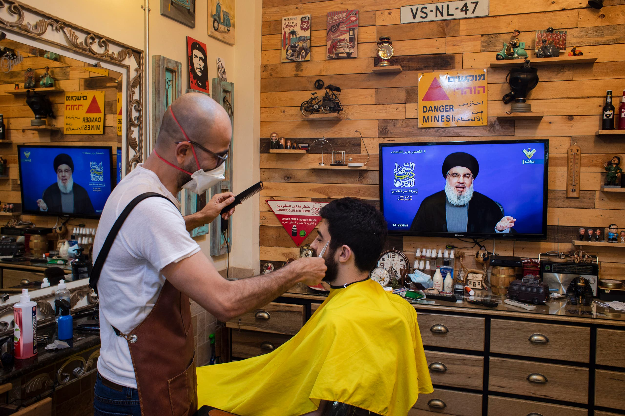 A barber wearing a mask listens to a speech by Hezbollah leader Hassan Nasrallah in the southern suburb of Beirut, Lebanon, Friday, May 22, 2020. (AP)