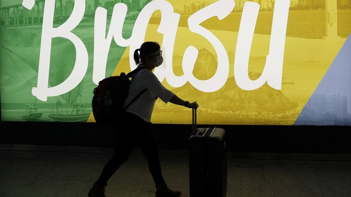 A traveller walks as she carries her bags at Guarulhos International Airport amid the outbreak of the coronavirus disease (COVID-19), in Guarulhos, near Sao Paulo, Brazil. (Reuters)