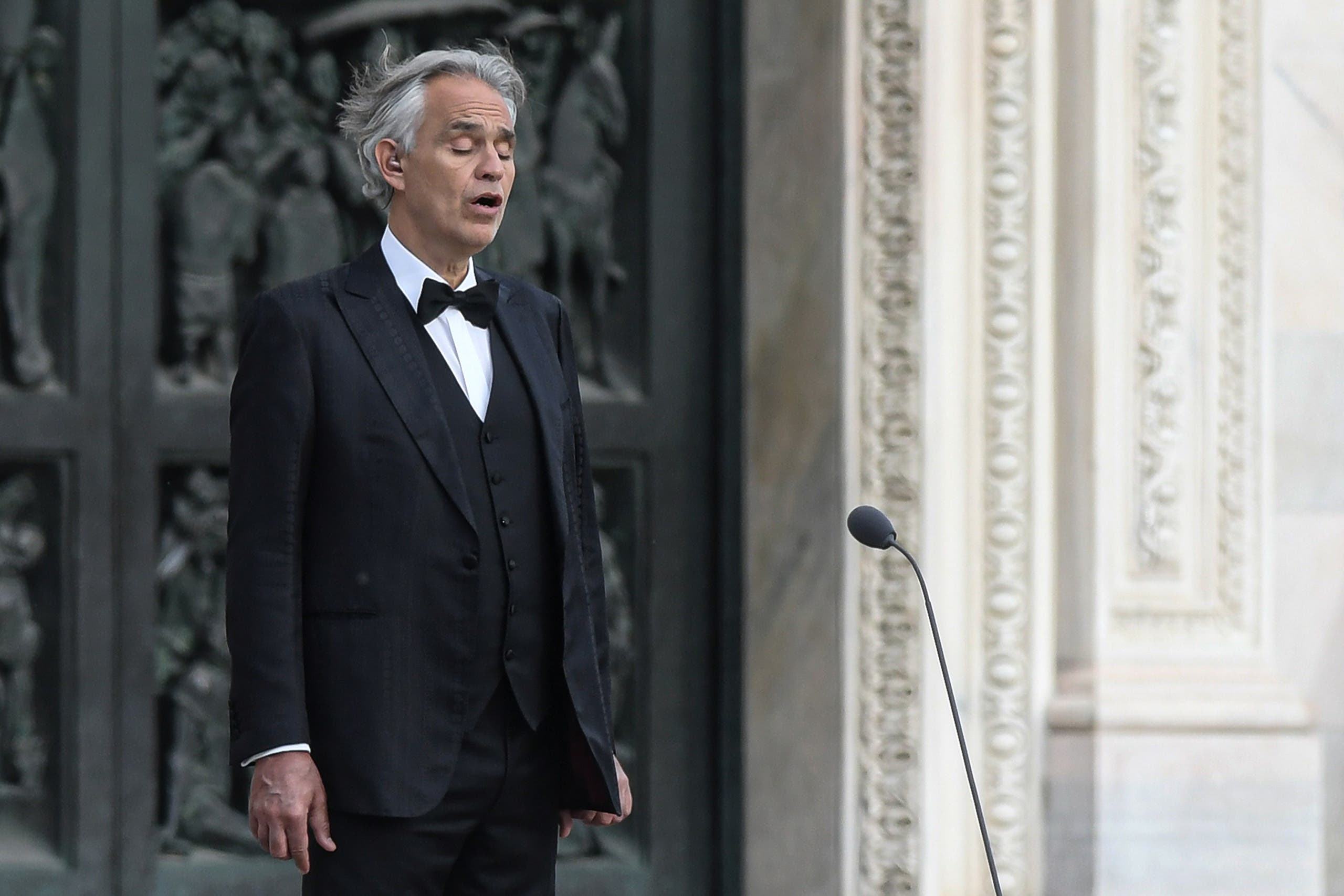 This photo taken on April 12, 2020 shows Italian tenor and opera singer Andrea Bocelli sing during a rehearsal on a deserted Piazza del Duomo in central Milan. (AP)
