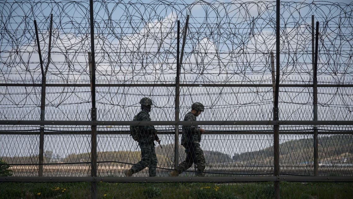 (FILES) This file photo taken on April 23, 2020 shows South Korean soldiers patrolling along a barbed wire fence Demilitarized Zone (DMZ) separating North and South Korea, on the South Korean island of Ganghwa. North Korean troops fired multiple gunshots towards the South in the Demilitarized Zone dividing the peninsula on May 3, 2020, prompting South Korean forces to fire back, Seoul said.