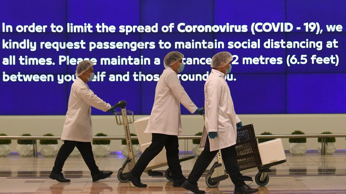 Employees at Dubai International Airport, walk past a poster reminding passengers to keep a safe distance from each other, after the resumption of scheduled operations by the Emirati carrier Emirates airline, amid the ongoing novel coronavirus pandemic crisis, on May 22, 2020.
