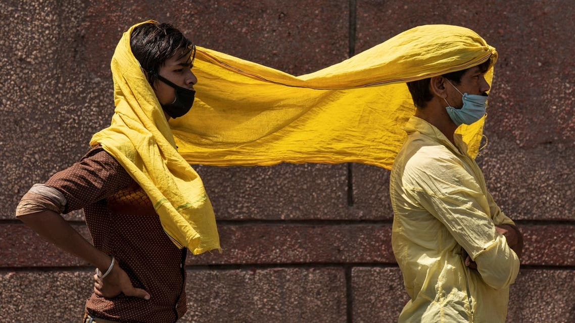 Migrant workers cover themselves with a scarf, to protect from heat as they wait to get registered before boarding a train to their home state of eastern Bihar, during an extended lockdown to slow the spreading of the coronavirus disease (COVID-19), in New Delhi, India, May 21, 2020. REUTERS/Danish Siddiqui
