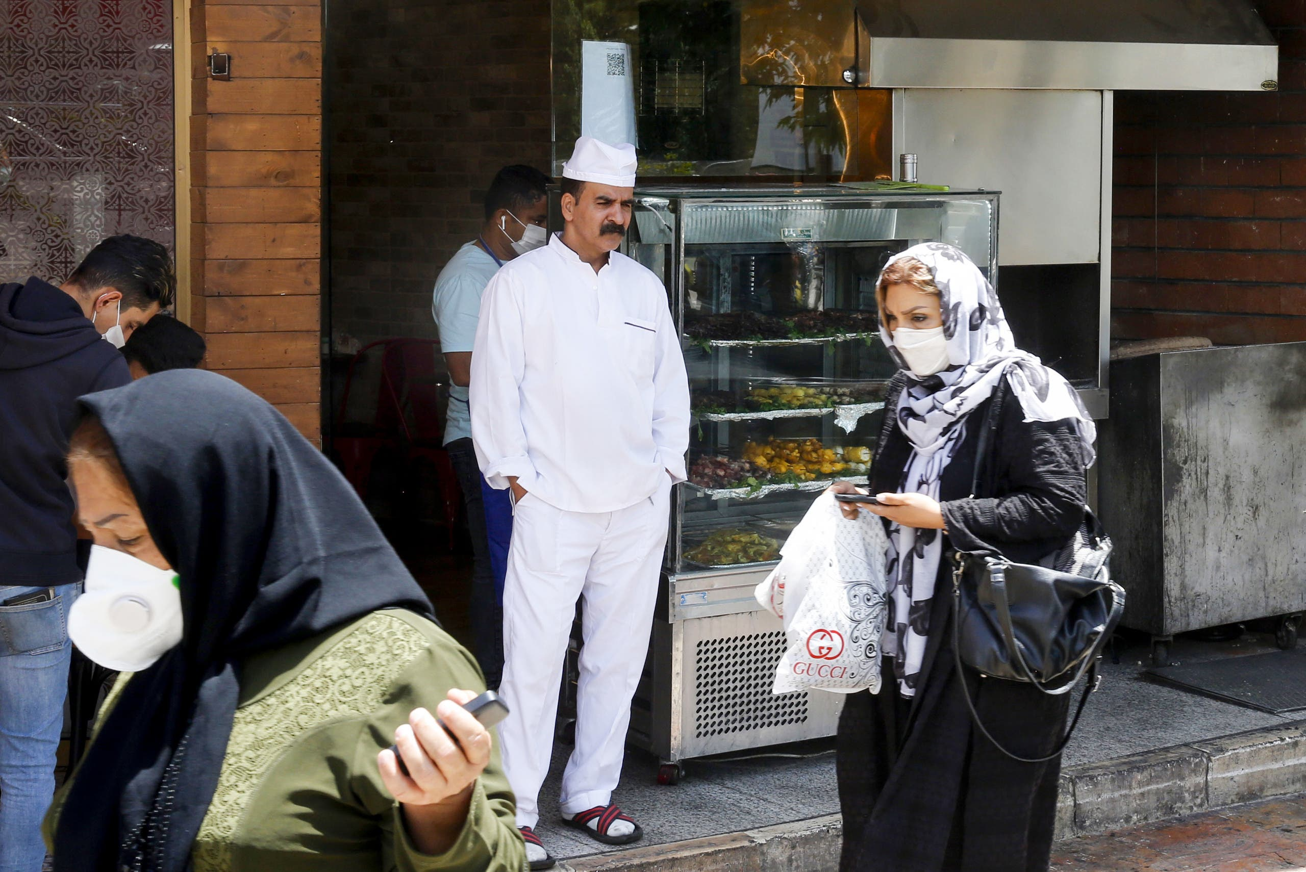 Iranians pass by a restaurant in the capital city of Tehran, on May 26, 2020. (AFP)