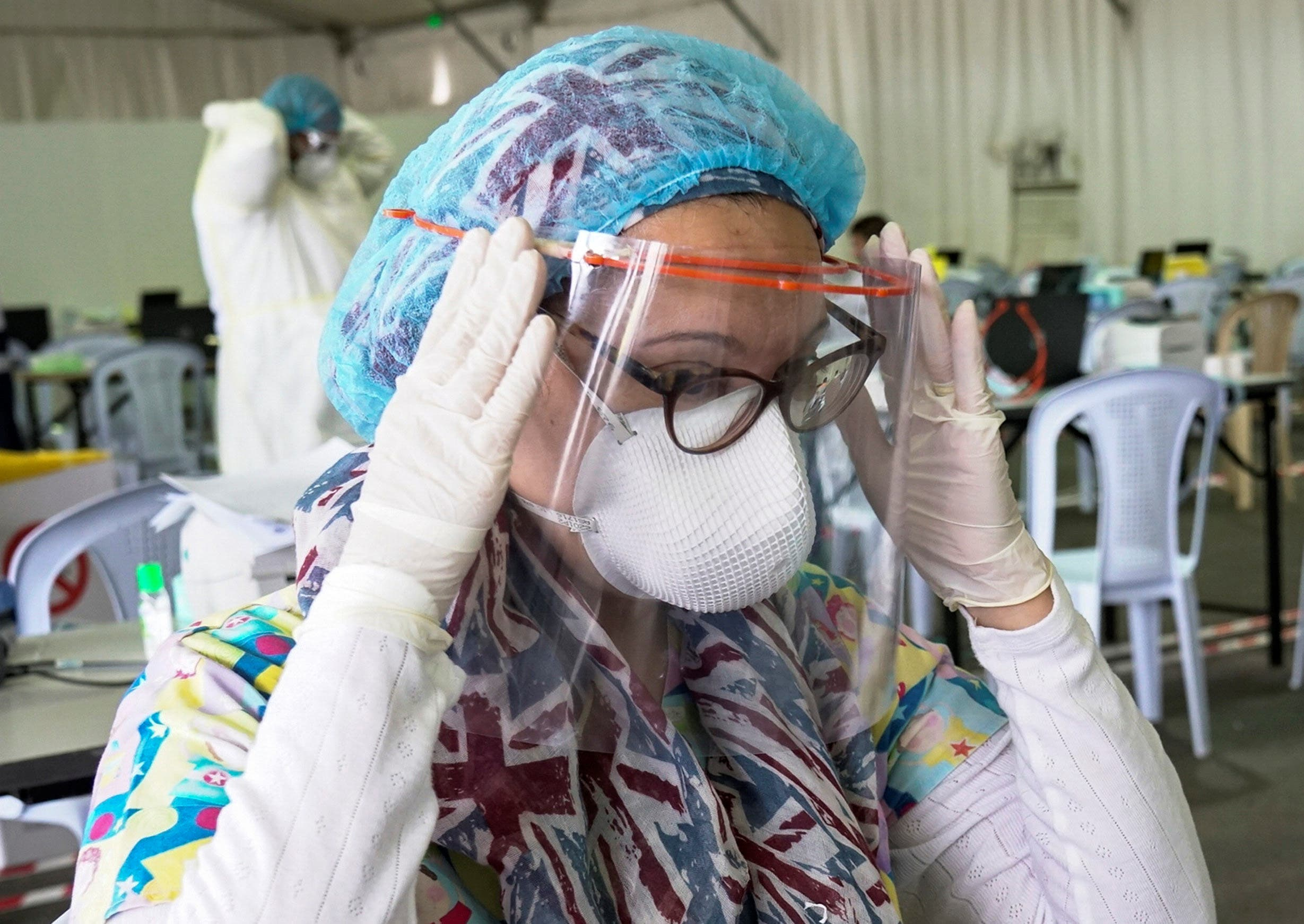طبيبة كويتية تضع قناعاً واقياً قبل فحص مواطنين تم إجلاؤهم في مطار الكويت (أرشيفية)