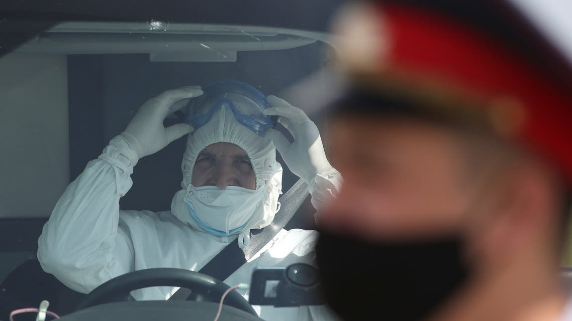 A specialist wearing protective gear and a law enforcement officer with a face mask are seen upon the arrival of a plane carrying Kyrgyz citizens, who came from Japan and South Korea amid the outbreak of the coronavirus disease (COVID-19), at an airport in Almaty, Kazakhstan May 14, 2020. REUTERS/Pavel Mikheyev
