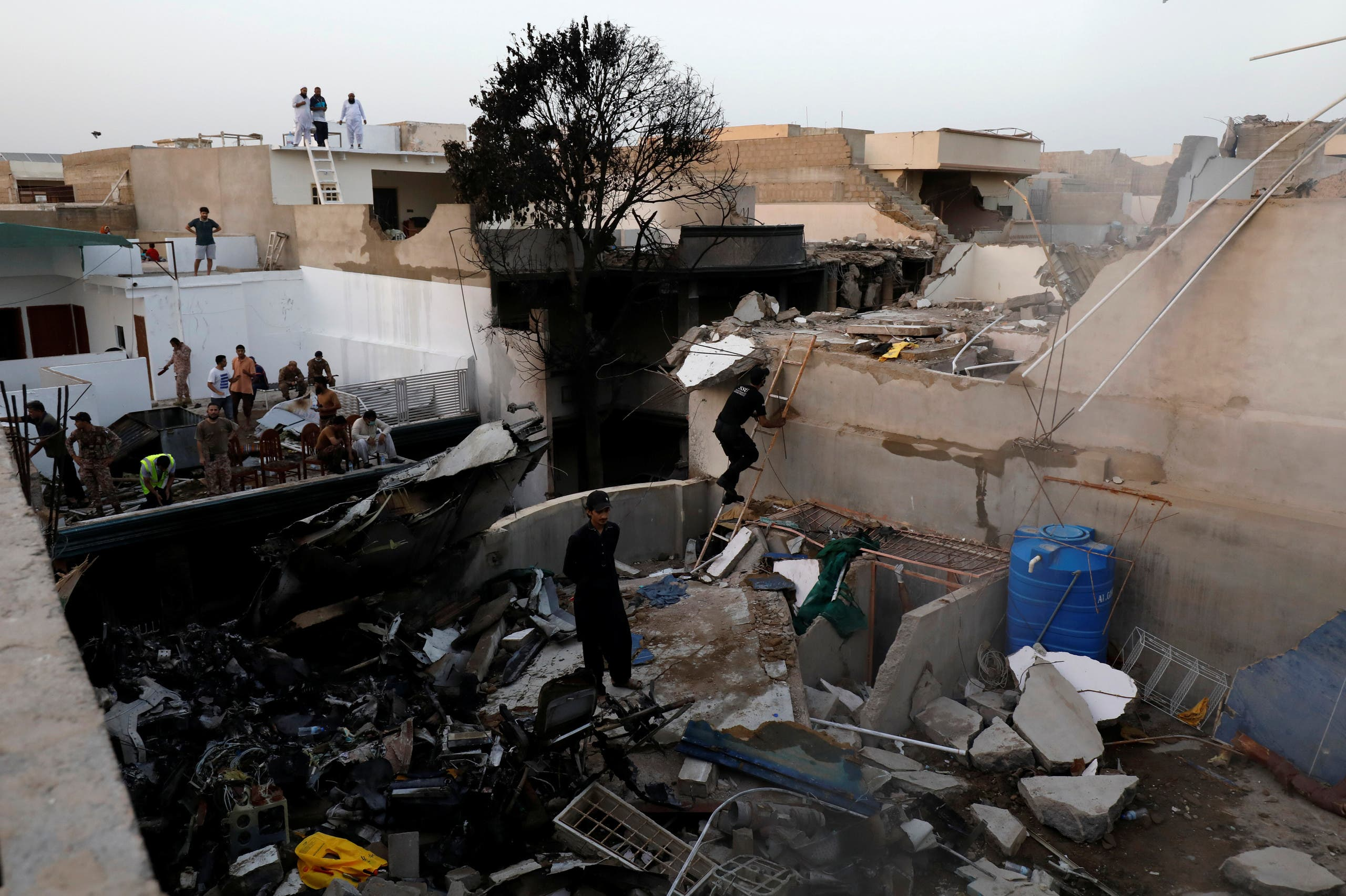 People stand on a roof of a house amidst debris of a passenger plane, crashed in a residential area near an airport in Karachi, Pakistan May 22, 2020. (Reuters)
