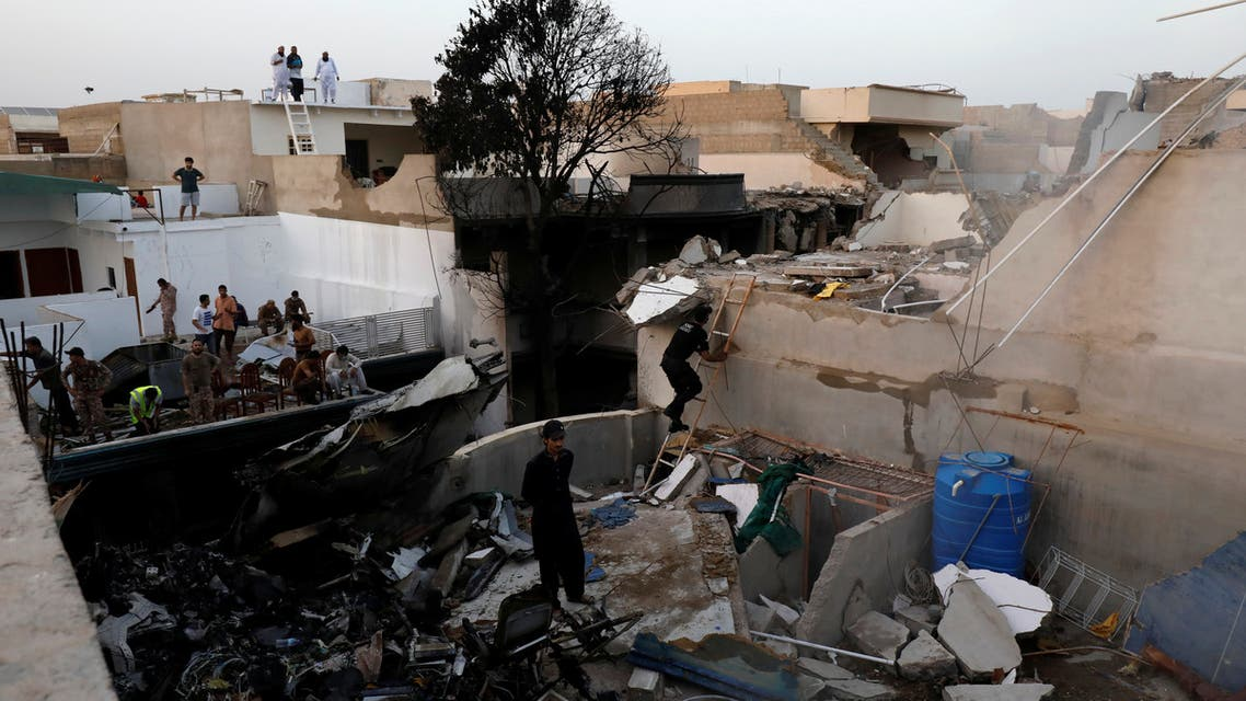 People stand on a roof of a house amidst debris of a passenger plane, crashed in a residential area near an airport in Karachi, Pakistan May 22, 2020. REUTERS/Akhtar Soomro