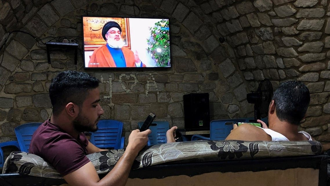 Men hold their phones as they watch Lebanon's Hezbollah leader Sayyed Hassan Nasrallah speak on television inside a coffee shop in the port city of Sidon, Lebanon July 12, 2019. (Reuters)
