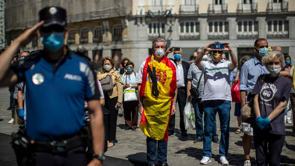 People hold a minute of silence for the victims of COVID-19 at Sol square in downtown Madrid, Spain, Wednesday, May 27, 2020. Flags are flying at half-mast on more than 14,000 public buildings in Spain as the European nation holds its first of 10 days of national mourning for the victims of the coronavirus. (AP Photo/Manu Fernandez)