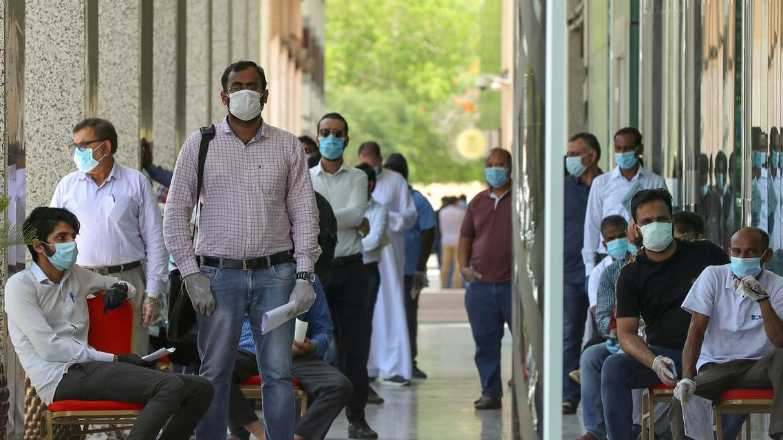 People wearing protective masks queue for services in Qatar's capital Doha, on May 17, 2020, as the country begins enforcing the world's toughest penalties for failing to wear masks in public while it battles one of the world's highest coronavirus infection rates. More than 30,000 people have tested positive for COVID-19 in the tiny Gulf country, 1.1 percent of the 2.75 million population, although just 15 people have died. Violators of the new rules will face up to three years in jail and fines of as much as $55,000.
