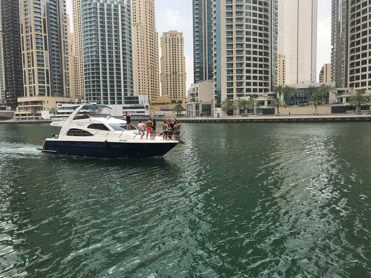 People react as they take pictures on a yacht during the first day of Eid al-Fitr, following the outbreak of the coronavirus disease (COVID-19), in Dubai. (Reuters)