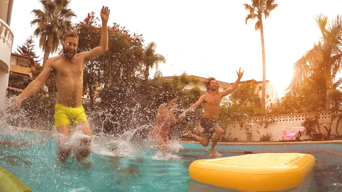 Group happy friends jumping in pool at sunset time - Crazy young people having fun making party in exclusive tropical house - Summer holidays vacation and youth culture lifestyle concept stock photo